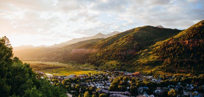 Blick auf ein Dorf in einem Tal bei untergehender Sonne