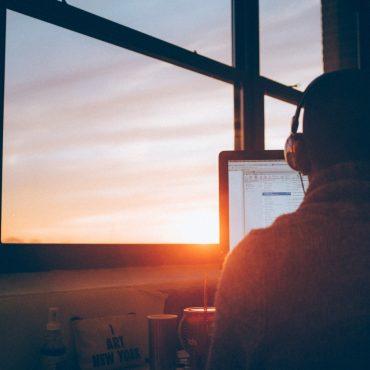 Rückansicht auf einen Mann, der an einem Bildschirm arbeitet und Kopfhörer aufhat. Hinter dem Bildschirm bricht sich die untergehende Sonne.