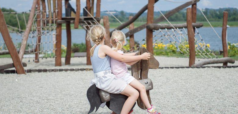 Zwei Mädchen schaukeln auf einem Schaukelpferd. Ihre Gesichter drehen sie zur Seite, so dass man sie nicht erkennen kann.