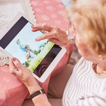 Blick aus der Vogelperspektive auf eine ältere Frau, die ein Tablet in der Hand hält.