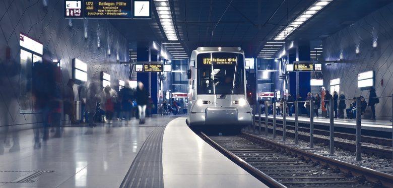 U-Bahn Station in die eine U-Bahn eingefahren ist. Von den Menschen sieht man auf dem Bahnsteig nur die Silhouetten.