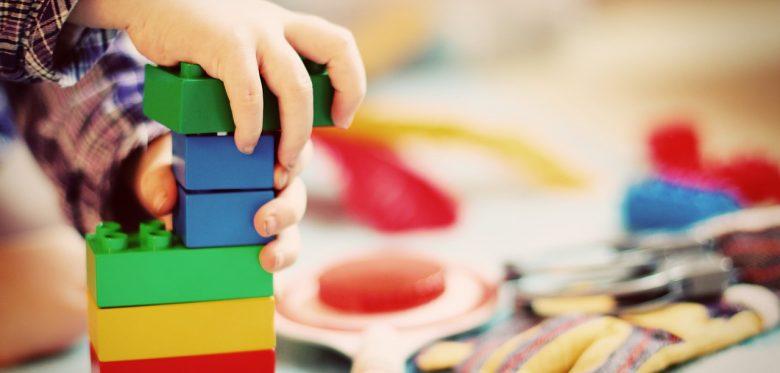 Eine Kinderhand spielt mit Duplosteinen