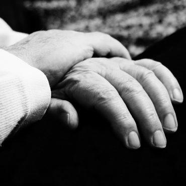 Schwarz-weiß Foto. Eine etwas jüngere Hand greift nach der Hand einer älteren Person.