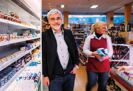 Heinz Freiy lehnt sich lächeln an eine Kühltheke im Dorfladen