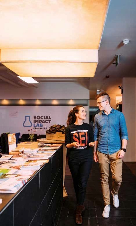 Ein junger Mann und eine junge Frau unterhalten sich im Gehen in einem großen Büroraum. Im Hintergrund das Schild: Social Impact Lab