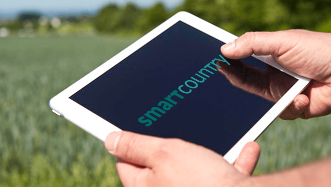 Zwei Männerhande halten ein Tablet. Darauf zu sehen ist der Schriftzug Smart Country. Im Hintergrund sieht man unscharf ein Feld.
